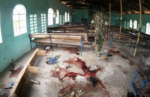 A Kenyan policeman walks inside the African Inland Church after an attack in Garissa