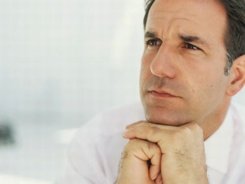 Mature man with hands on chin,looking away,close-up