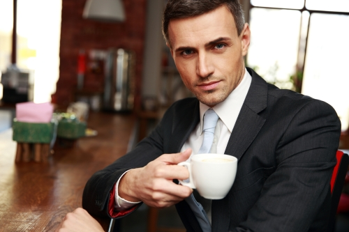 Confident businessman drinking coffee in cafe